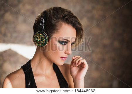 Lovely lifestyle girl with tanned skin and white hair listening to music on headphones. Female lifestyle beauty portrait of a beautiful makeup. Enjoying good music lifestyle. Lifestyle concept