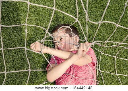 boy tangled in soccer net. The kid lying on the football field and tries to get out of the net. Top view