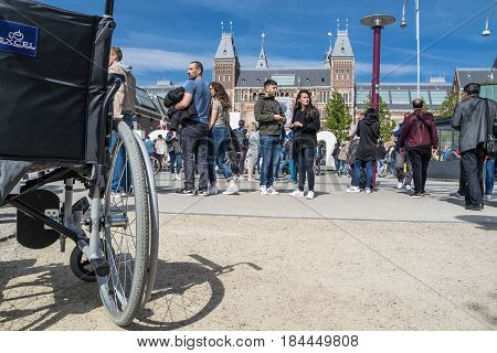 AMSTERDAM, NETHERLANDS - APRIL 31, 2017 - Wheelchair standing in the middle of the crowd on museumplein in Amsterdam in front of the I Amsterdam letters