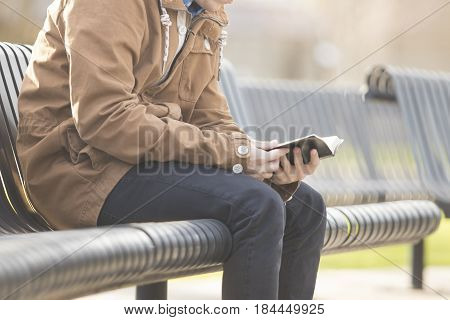 Handsome teenage boy in outdoors reading Bible