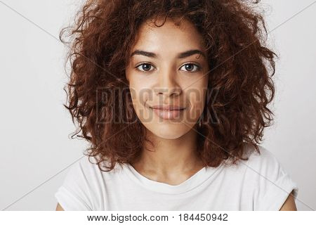 Close up portrait of beautiful african girl smiling looking at camera. Isolated on white background.