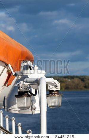 Signal lights on the river cruise ship. Lifeboat, clouds and riverside in the background.
