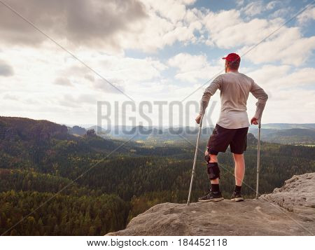 Hiker In Grey T-shirt, Medicine Crutch And  Leg Fixed In Immobilize Achieved Mountain Peak.