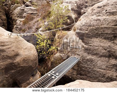 Iron Ramp In Rock, Tourist Ladder. Iron Twisted Rope Fixed In Block.  Climbers Way Via Ferrata.