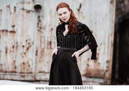 Striking trendy girl with long red hair in black trendy clothes. A trendy woman in a black dress and trendy jacket posing on a background of winter nature. Female street fashion style. Beautiful elegant trendy model
