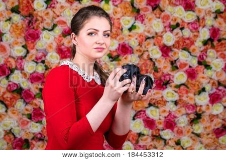 Happy brunette photographer woman in sexy red blouse holding camera in a studio on a floral wall background