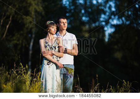Beautiful girlfriend with dark hair and brown eyes with a wreath on head in summer dress hugging a man in awhite shirt on a green background. Loving couple in the forest on a sunny day. To love each other. Nice girlfriend. To love girlfriend. Concept with
