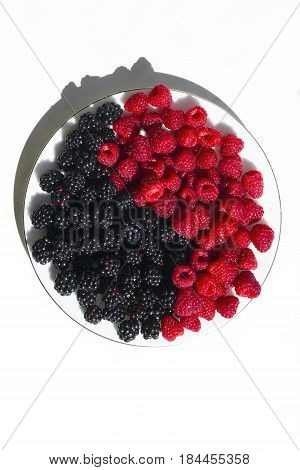 Fresh raspberries and blackberries on plate lined with symbol of yin and yang isolated on white background top