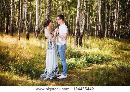 Beautiful couple. Couple in forest. Girl with dark hair and brown eyes with a wreath on head in summer dress hugging a man in awhite shirt on a green background. Loving couple in the forest on a sunny day. Couple love each other. Nice couple. Couple relax