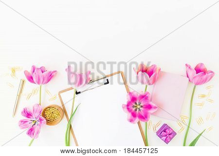 Beauty blog concept. Workspace with clipboard, notebook, pen, pink tulip flowers and accessories on white background. Flat lay, top view.