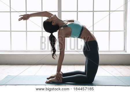 Young woman doing yoga asana exercise indoors near window