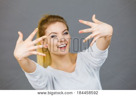 Happy proud young woman showing her hands in front of her face studio shot grey background.