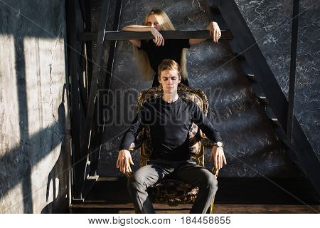 A young serious man and young serious blonde woman with long hair. Problems and difficulties in relations. Difficult situation in life. Conceptual photography. Actor play. Hard shadows. Show feelings. Hide feelings. Serious girl. Serious couple