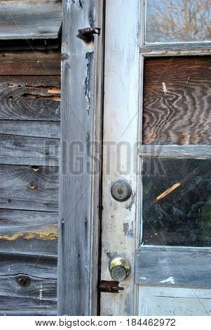 An abandoned home with door and broken windows.