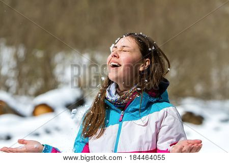 A young girl in a multicolored jacket with her eyes closed rejoices in the snow that falls on her face.