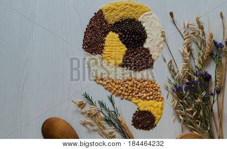 Beautiful top view of a scattering on cereals and grains on a white background. Wooden saltcellar and spoon for the preparation of healthy dishes.