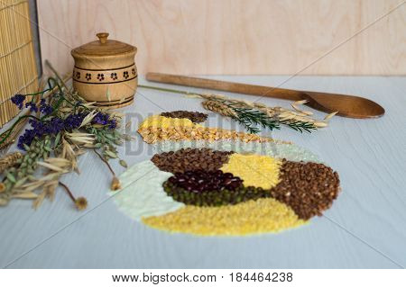 Buckwheat grain, rice, corn, pea, semolina and lentil on a white wooden background.