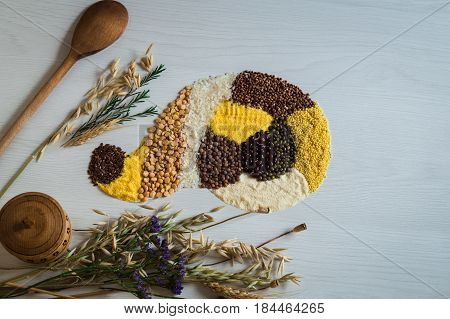 Top view of a scattering on cereals and grains on a white background. Wooden saltcellar and spoon for the preparation of healthy dishes.