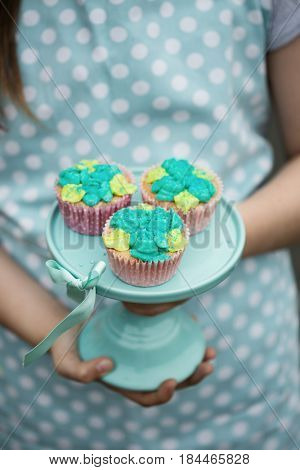 Frosted cupcakes on a turquoise cake stand