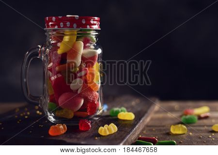 a mason jar full of candies with different flavors and colors, on a rustic wooden table