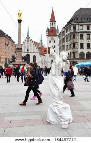 Munich, Germany - April 29, 2013: Walking people and street artist on Marienplatz square in Munich