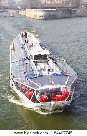 Paris, France - March 05, 2011: Tourist recreational boat floats down the Seine river in Paris