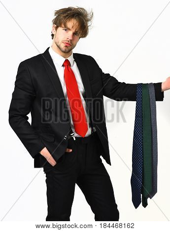 Bearded man short beard. Caucasian stylish serious macho with moustache in elegant suit red tie shirt with suspenders holding dark ties posing at studio isolated on white background