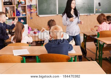 Young woman teacher teaches children at the elementary school