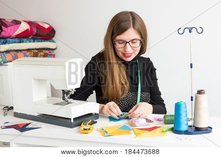 needlework and quilting in the workshop of a young woman - pretty young tailor woman stitching by needle pieces of colorful fabrics at the workplace of thread, needles, a sewing machine and fabrics