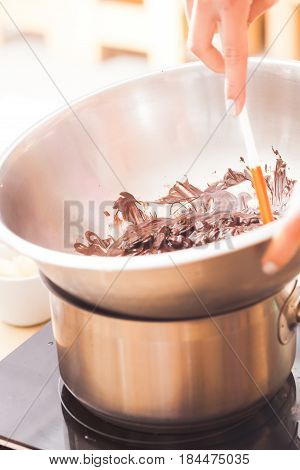Melting thick brown chocolate in a metal bowl