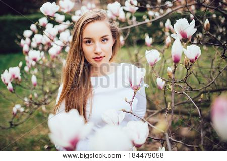 Lovely Girl Standing Near Magnolia Blossoming Flowers, Stands In White Pink Dress A Small Smile Smil