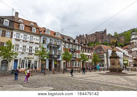 HEIDELBERG GERMANY - MAY 3 2013: People walking on Kornmarkt square in Heidelberg old town Germany. Madonna statue on foreground and Heidelberg castle on the background