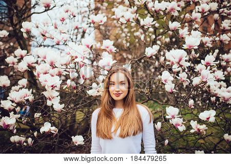 Beauty Woman Standing On Background Magnolia Blossoming Flowers.