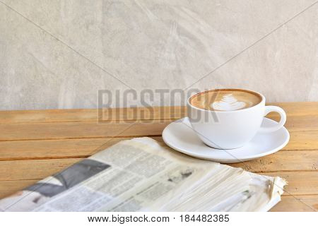Newspaper and Latte Cappuccino on wood in Coffee Shop Cafe