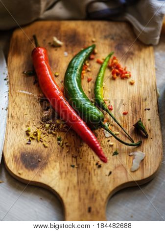 Red And Green Chilli Peppers On Wooden Cutting Board.