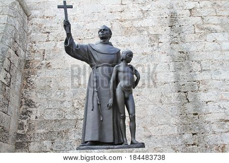 Junipero Serra religious statue in the Saint Francis of Assisi square. Catholic figure holding a a Christian cross and a young boy