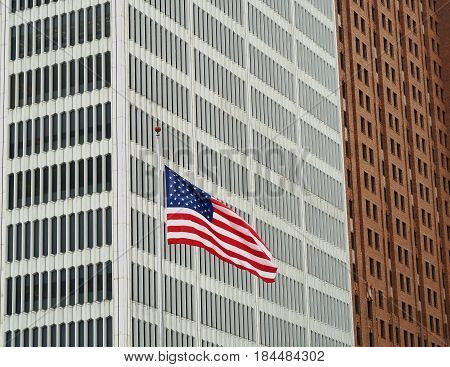 DETROIT - May 1, 2017. The juxtaposition of an American flag and skyscrapers of contrasting styles make for an unusual architectural abstract. The flag flies in front of the One Woodward Building, next to which is the Guardian Building.