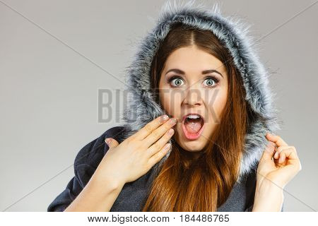 Shocked woman wearing dark poncho coat with furry hood. Winter fashion trendy clothing outfits concept.