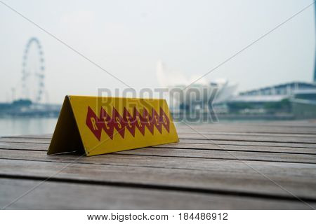 Restaurant reserved table sign with Singapore landscape in the background during cloudy day