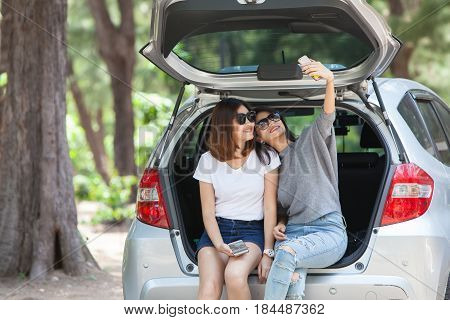 Friends sit in the open back of a car and take photo