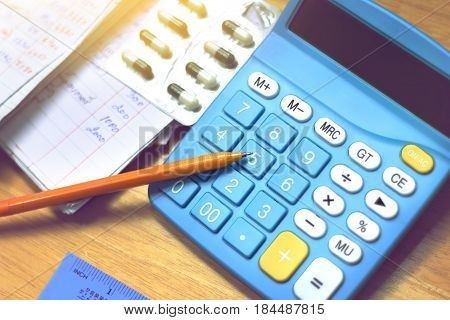 ball pen on calculator and household bills with medicine tablets in the panel headache from accounting