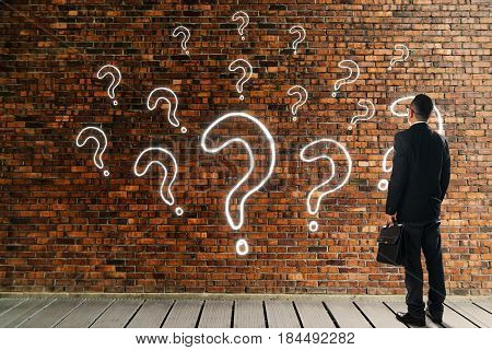 Businessman looking and thinking in front of a brick wall with the question marks icon . Business question concept .