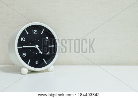 Closeup black and white alarm clock for decorate in a quarter to five o'clock or 4:45 p.m. on white wood desk and cream wallpaper textured background with copy space