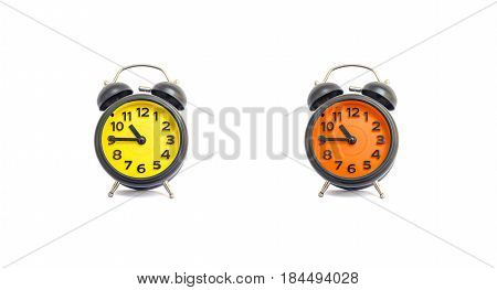 Closeup yellow alarm clock and orange alarm clock for decorate show a quarter to eleven o'clock or 10:45 a.m. isolated on white background