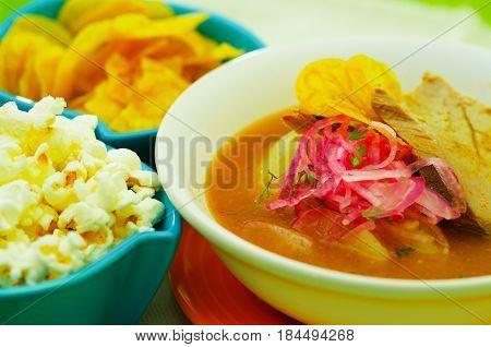 Delicious encebollado fish stew from Ecuador traditional food national dish closeup with popcorn.