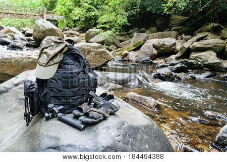 Hiking sandals backpack cap and camera on a big rock near water stream concept for trekking trip.