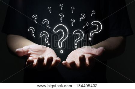 Businessman holding drawn question marks in his hand with dark background Business question concept .