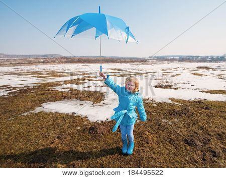 the little happy girl with umbrella outdoor