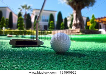 Mini golf scene with ball and club. Sunny day at resort park