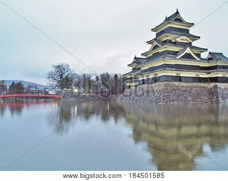 Matsumoto Castle in Nagano Prefecture, Japan with yellow light up in the evening. The building is also known as the Crow Castle due to its black exterior, It is listed as a National Treasure of Japan.
